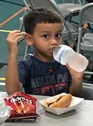 Kids get grilled hot dogs, chips, a drink and cookies at our Backpack Event