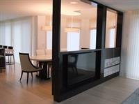 A room divider, made of Madagascar ebony, that hides a TV in a contemporary home.