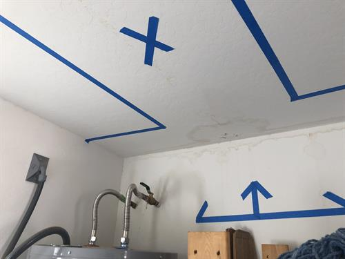 Marking areas of ceiling showing moisture.