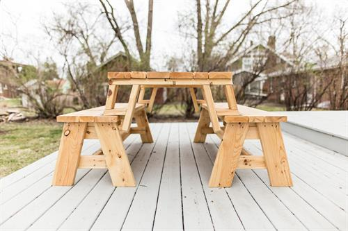 Convertible outdoor picnic table converts from a table to two individual benches.
