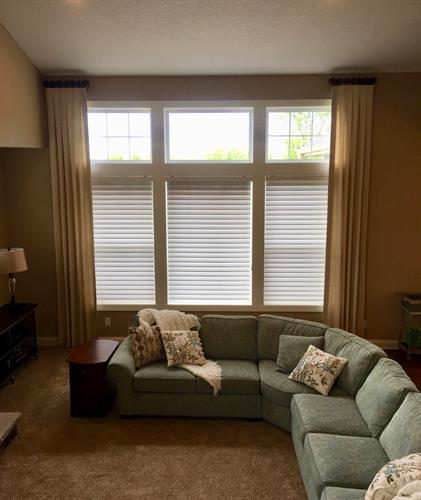 Custom length draperies help to enhance the height of the room while framing the windows and softening the overall look of the wall.