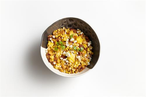 Elote (Mexican street corn) tossed in a citrus aioli, cotija cheese, corn nuts, and cilantro.