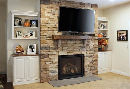 Classic cabinetry harmonizes with the texture and color of the stone fireplace.