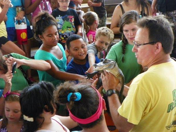 Tim Reno introduces his baby alligator to children at the Summer Reading Program at Big Lagoon State Park Amphitheatre sponsored by The Friends.