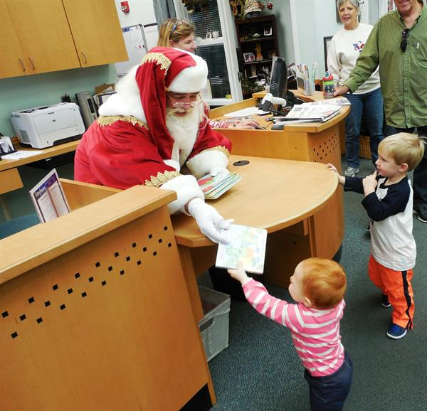 Santa Claus visited the Southwest Branch Library. Here he is checking out books to some little patrons.