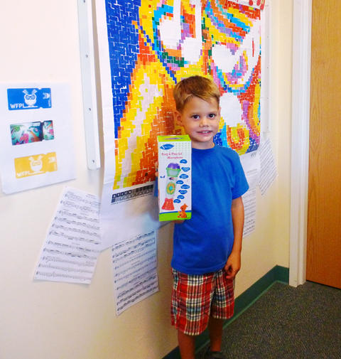 Niall shows his prize in the Summer Reading Club at the Southwest Branch Library