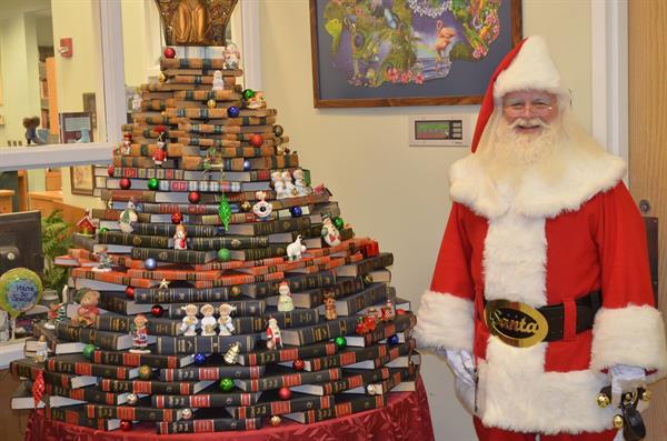 Santa next to Mrs. Melanie's book tree at The Southwest Branch Library