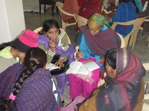 Women in Northern South Asia discussing a community problem from a Biblical perspective.