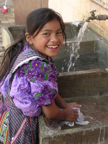 A young Guatemalan girl enjoying the benefits of clean water her family and community how has access to.