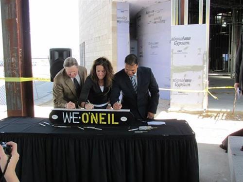 Mayor Sam Cobb, Kim O'Neil, and Rafael Verde signing beam