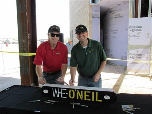 Members of W.E. O'neil signing the beam