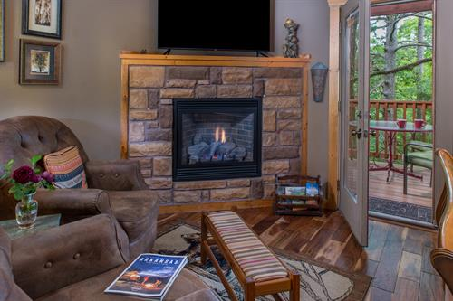 Inside of all cabins and cottages. A fireplace and TV, two comfortable chairs or a loveseat.