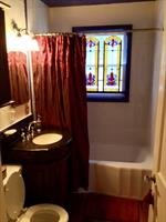 Stained glass from an old church adds elegance to our bathroom