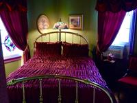 Rose bedroom with antique brass bed and stained glass