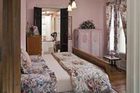 Sarah Bernhardt's elegant bedroom with king bed and birds-eye maple antique furnishings