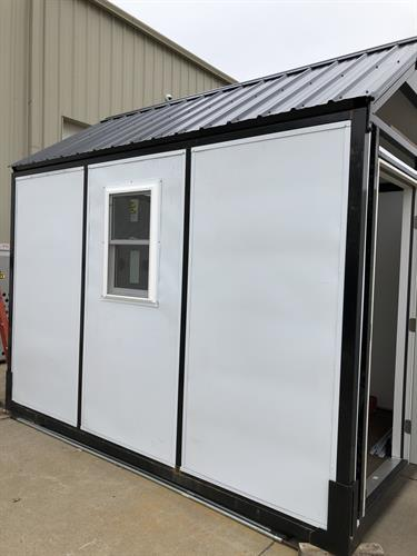 Structure with insulated hard side panels, door, window, electrical package, and heating/air conditioning unit.