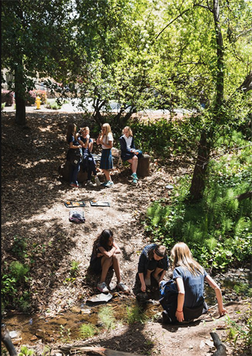 Every bit of our 14-acre campus is made for our students' exploration, growth, and inspiration. Students relax near our on-campus creek.
