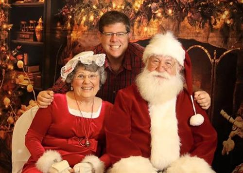 Byron poses with Santa and Mrs. Claus at one of the dozen annual pictures with Santa events he covers.