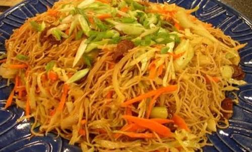 Filipino Pancit. Meat and vegetables marinated and cooked with Casian Spices before adding Filipino Rice Noodles.  Squeeze on the lime for that added zing.