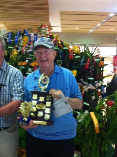 Rotarian Gerry taking the prize for his winning orchids