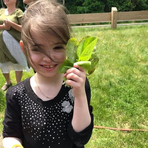 Gloucester student with lettuce that she planted, grew, and harvested in her school garden for Salad Days