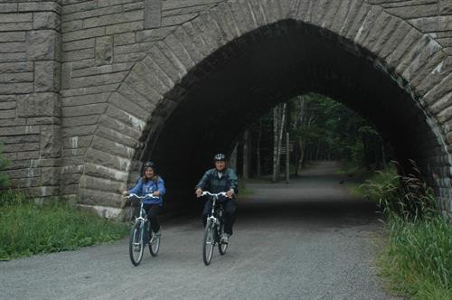 Bikers on the carriage roads emerge from under one of the Rockefeller bridges.