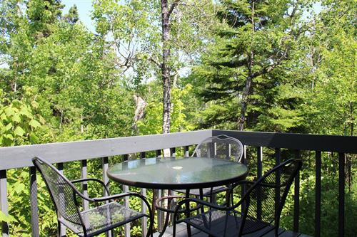 The deck of a Two Bedroom Condo, overlooking a creek and boreal forest