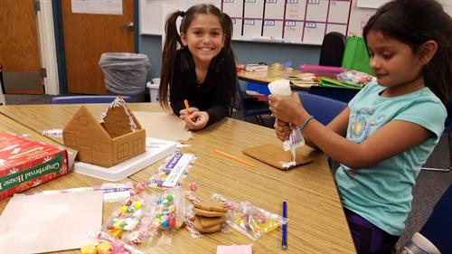Two of our 2nd grade students work together to make a gingerbread house during afterschool programming.