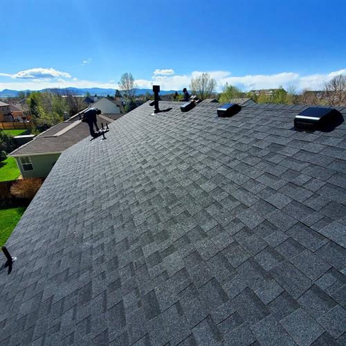 Putting the finishing touches on a newly installed roof. Don't you just love the sleek look of Owens Corning Onxy Black shingles?