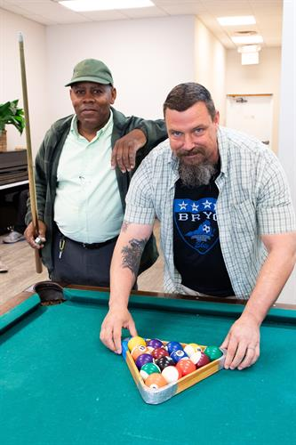 Interacting over a fun game of pool is relaxing and helps participants bond.