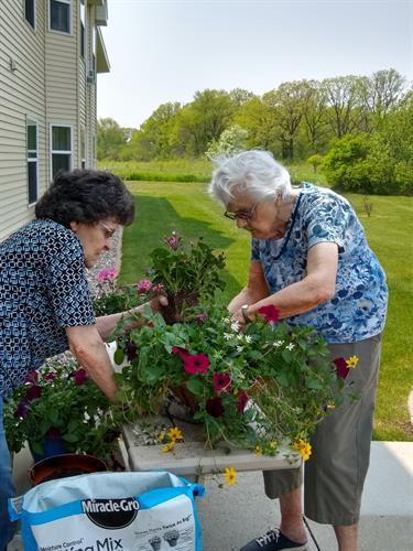 Mary and Helen are busy planting baskets to hang in the Memory Care Wandering Garden