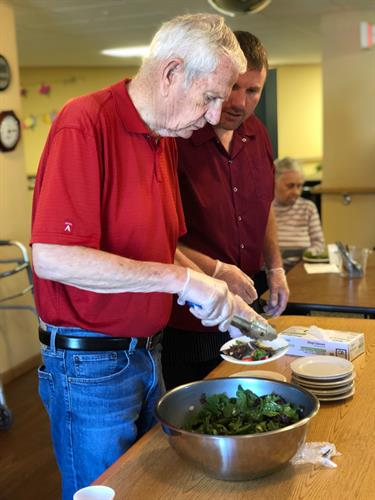 Jim Johnson is in his element helping Chef Chris make a Spring Berry Salad during a Wellness Event.  Jim use to serve as Kitchen Manager at Pioneer Home.