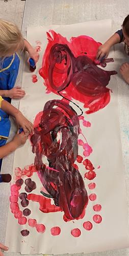Painting and exploring art through finger painting.