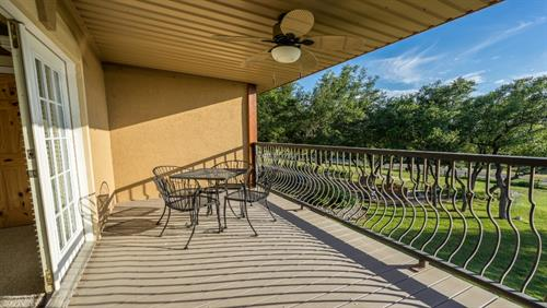 Outside of upstairs master bedroom on covered balcony with awesome lakefront views