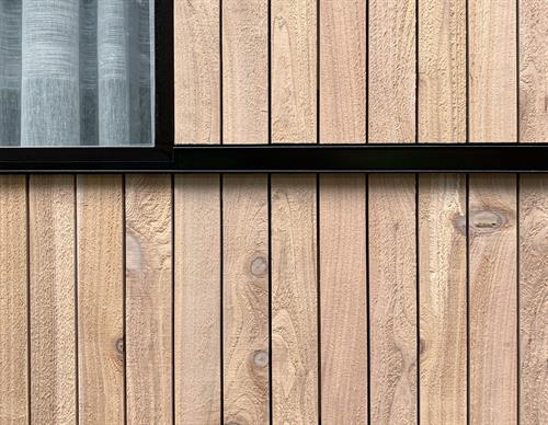 Detail of natural cedar rainscreen siding with blackened steel (completed 2020)