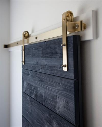 Weathered blue door with Brass Classic Flat Track hardware