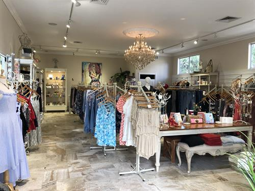 Entrance to store with grand chandelier and beautiful fashions with new arrivals weekly