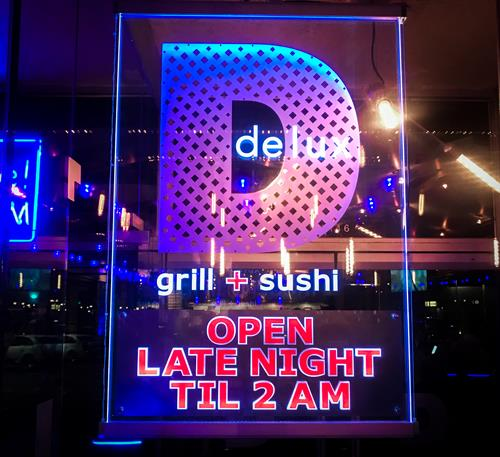 Delux sushi + grill restaurant sign