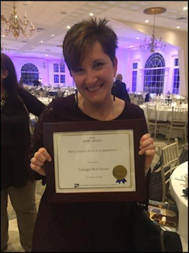 Director of Marketing, Kathy Bauer displaying award for Best Video for a Community at the 2019 HOBI Awards