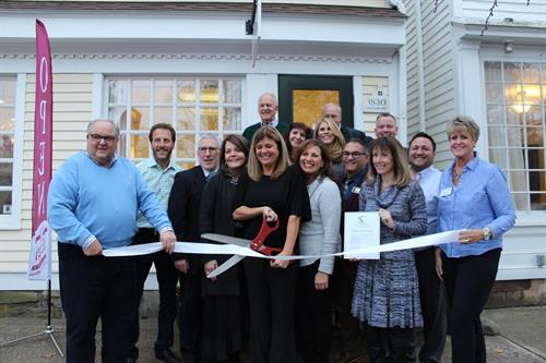 Stacy Calcagni of Guilford cutting the ribbon for Calcagni's Real Estate's Guilford office.