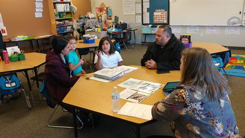 Promontory holds Student-Led Conferences instead of Parent/Teacher Conferences.  This student is presenting her portfolio of work to her parents and evaluating and communicating about the level of her own learning.