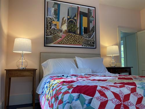 Main bedroom has windows on three sides and original art.