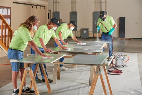 Bronz-Glow Team cleaning and coating HVAC Cabinetry with a 10-year FL UV coating.