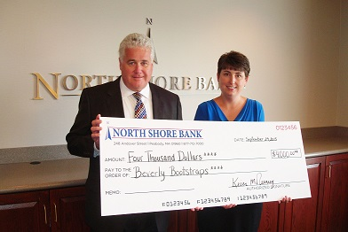 """North Shore Bank President and Chief Operating Officer Kevin M. Tierney, Sr. presents Heather Johnston, Beverly Bootstraps Director of Donor Relations with the first of five donations to the organizations """"Building Community. Together."""" Capital Campaign.  The Bank's total contribution over five-years will be $20,000.  The campaign is the first ever capital campaign for the organization and has been extremely successful in raising funds for the purchase and renovation of a new building."""
