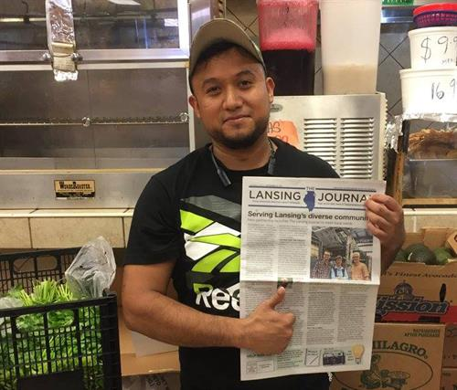 Gerardo Vidaure gives a thumbs-up to The Lansing Journal at Three Roosters grocery store.