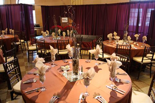 Brown satin tablecloth, tableware, centerpiece, & Chiavari chairs.
