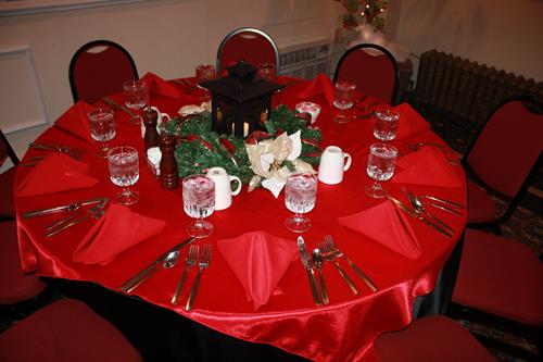 Black satin tablecloth with red overlay and a centerpiece with holiday garland and a lantern.