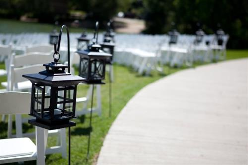 Black lanterns and white garden chairs at a wedding ceremony