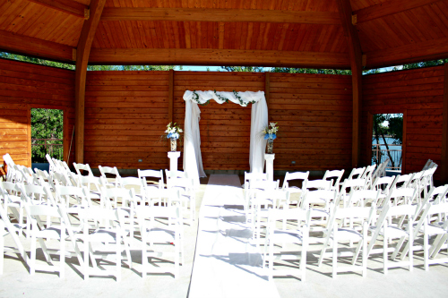 Fabric Wedding Canopy (Chuppah), floral pedestals with hydrangea and lily arrangement, and white garden chairs