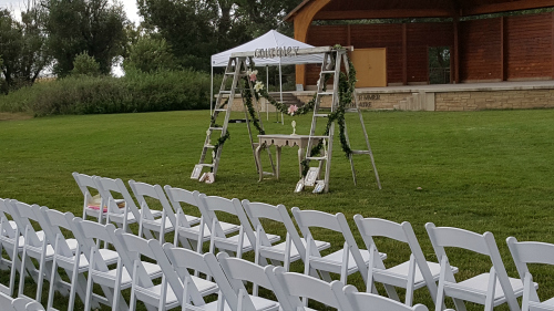 White garden chairs, small canopy, and floral garland by A-One Weddings & Events.